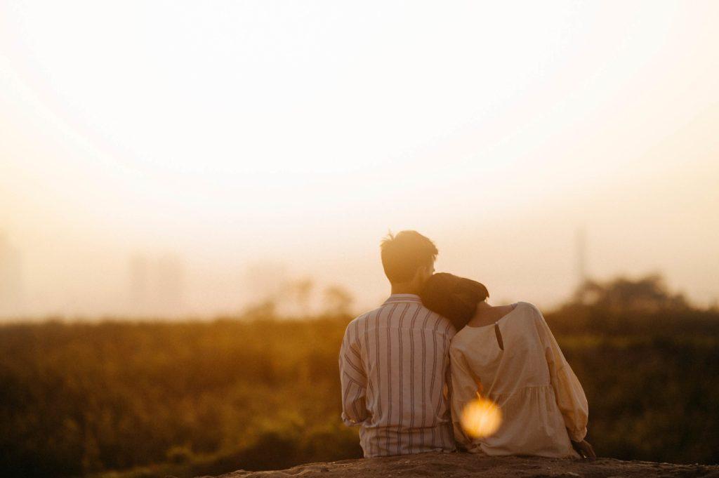 couple regardant le coucher de soleil lors de leur séance d'engagement